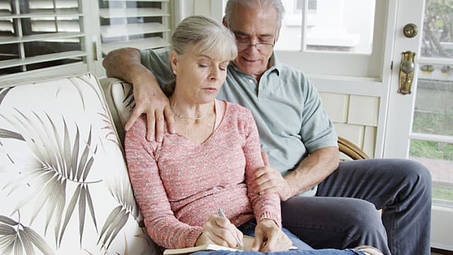 Mature couple sitting and writing in journal