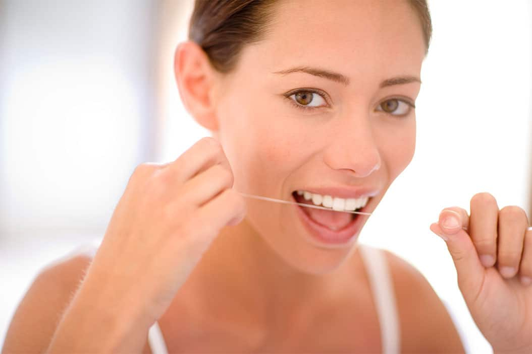 A woman flossing her teeth