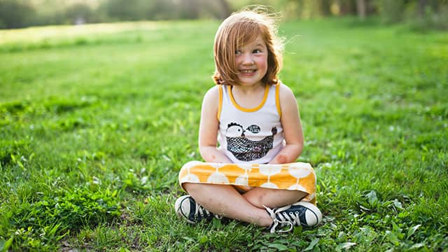 A girl is sitting on the grass and smiling