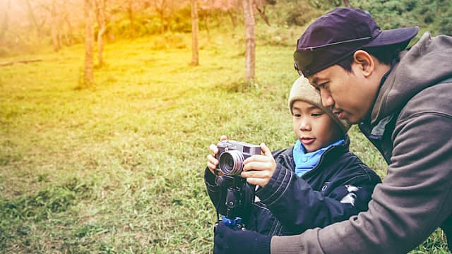 Happy family. Father teaching his son photographing outdoors in forest.
