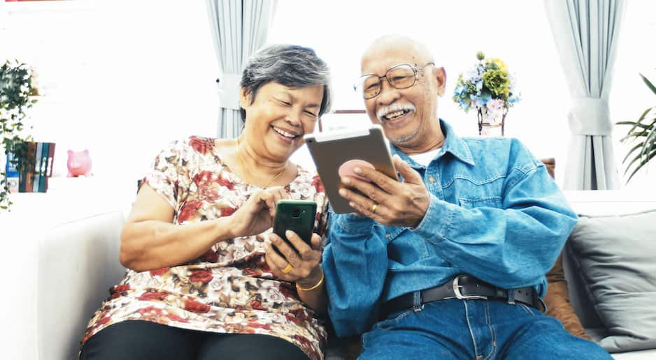 Older Couple Smiles and Looks at Phone on Couch