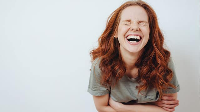 A young woman is laughing indoors