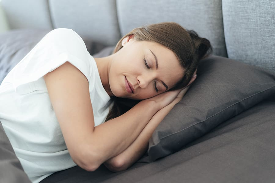 woman sleeping on a grey pillow on the couch