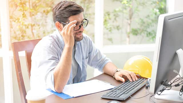 a man with black glasses using the computer