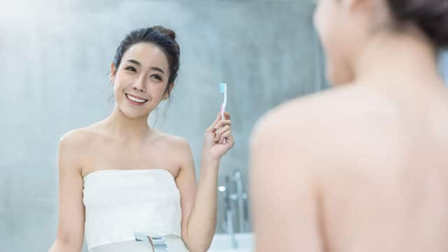 Young woman is looking at the mirror while holding a toothbrush