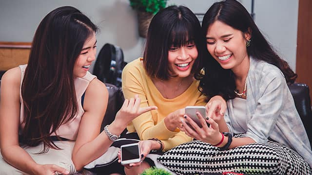 Three young women are looking at he smartphone, one of them wear braces