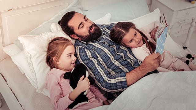 Father Reading Bedtime Story to Two Daughters