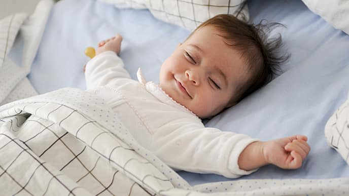 smiling newborn sleeping in crib