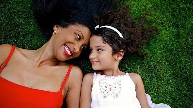 Mother laying in the grass with her biracial daughter