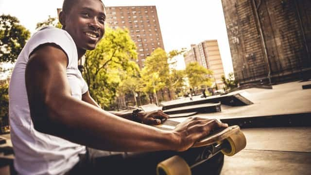 man smiling with skateboard