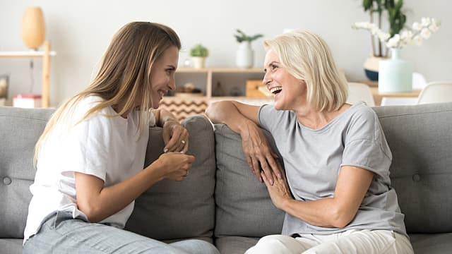 Cheerful old mother and young adult daughter talking laughing to