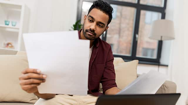 upset man with laptop and papers at home
