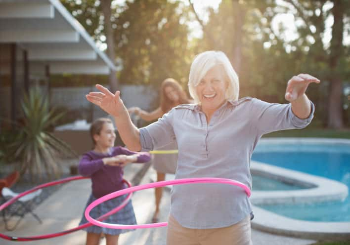 Woman hula hooping in backyard