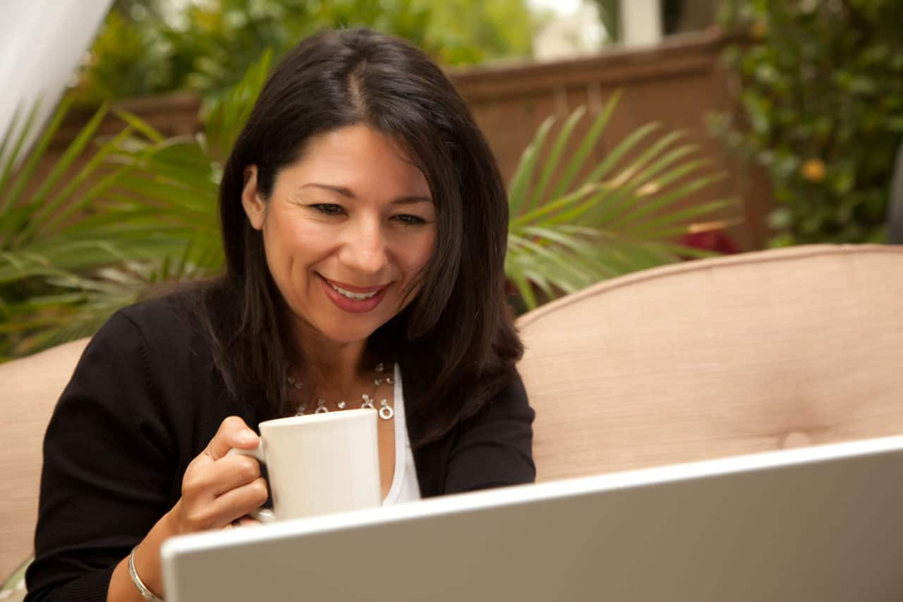 Woman with Coffee and Laptop On Her Patio