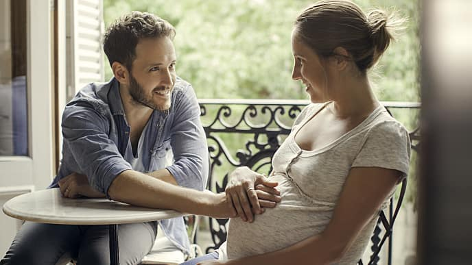 husband resting hands on pregnant stomach
