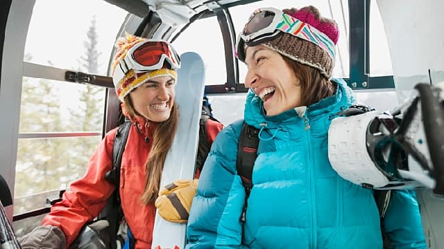 two people smiling on ski lift