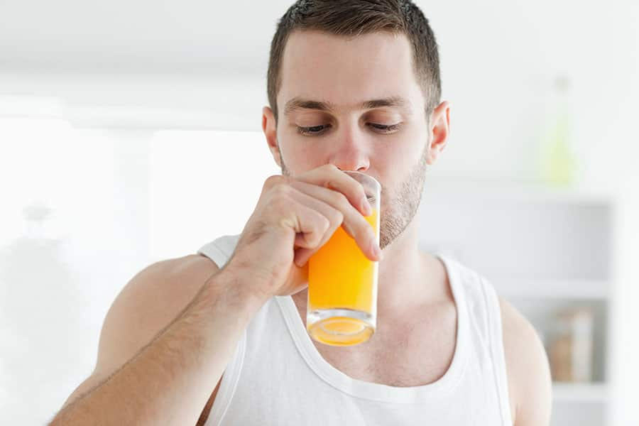 Man drinking juice in his kitchen