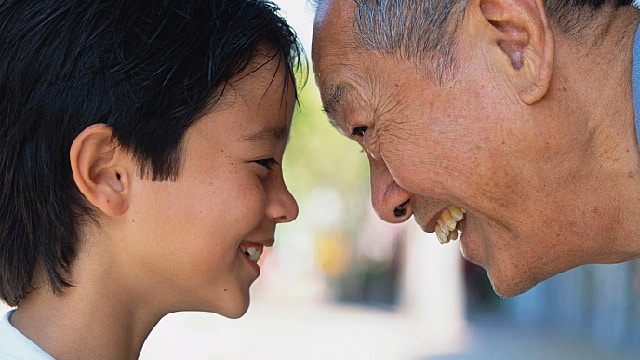 elderly Asian man smiling at child